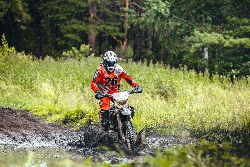 摩托车在泥水坑的竟赛者乘驾在他附近的森林水飞溅 库存图片