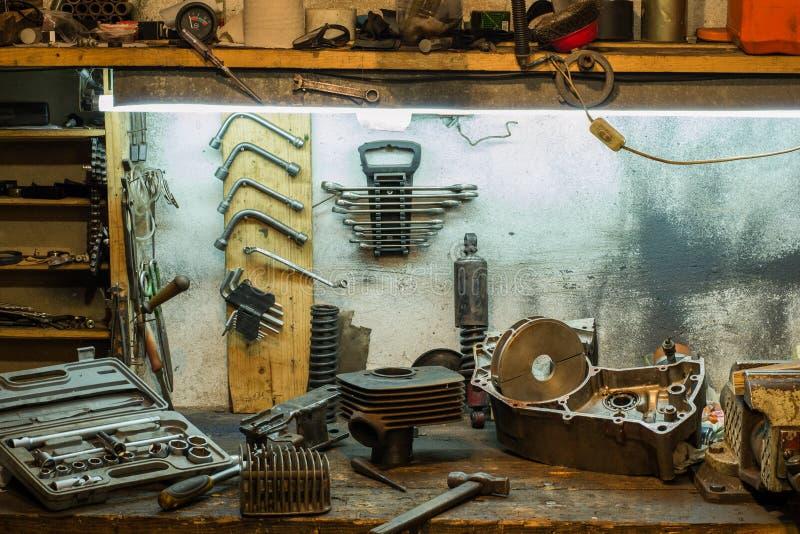摩托车在车库的桌面上分开 库存图片