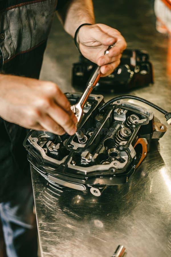 摩托车技工在服务站的引擎修理的特写镜头手 免版税库存照片