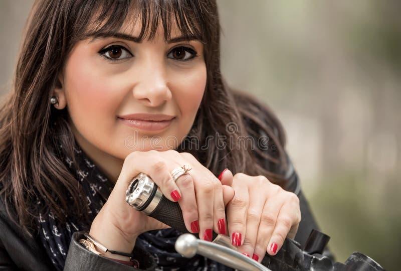 摩托车的可爱的妇女 免版税库存照片