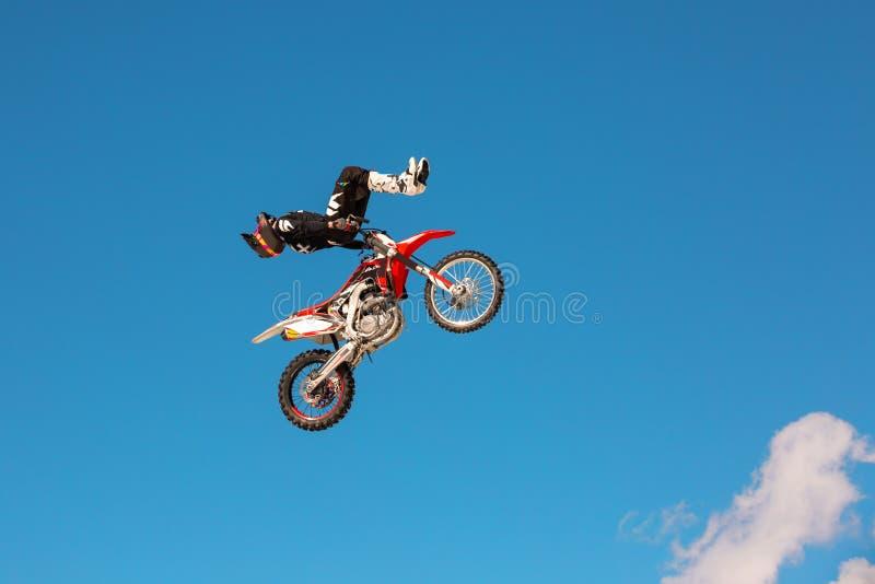 摩托车的竟赛者在跳板在飞行中参加横越全国的摩托车越野赛,跳并且离开反对天空 库存照片