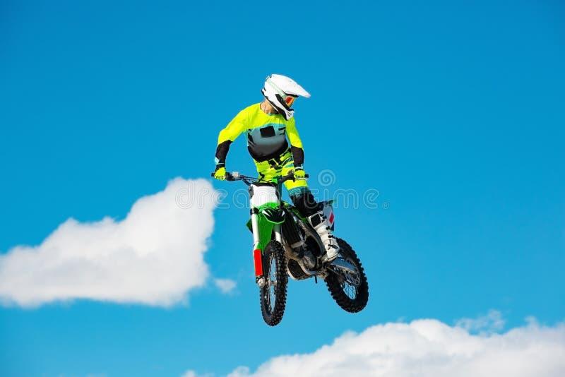 摩托车的竟赛者在跳板在飞行中参加横越全国的摩托车越野赛,跳并且离开反对天空 图库摄影