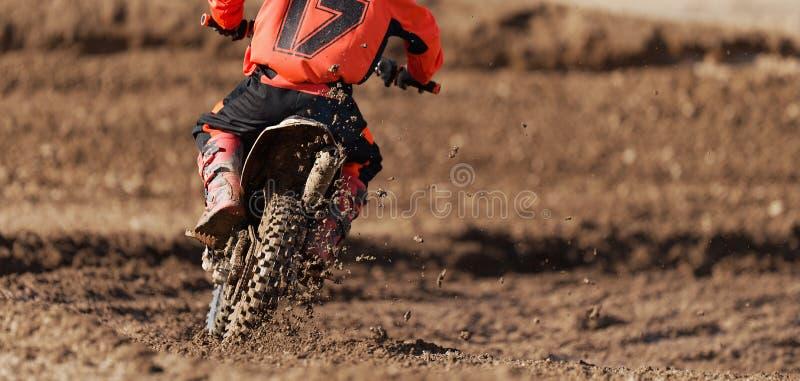 摩托车的竟赛者孩子参加摩托车越野赛种族 免版税库存照片