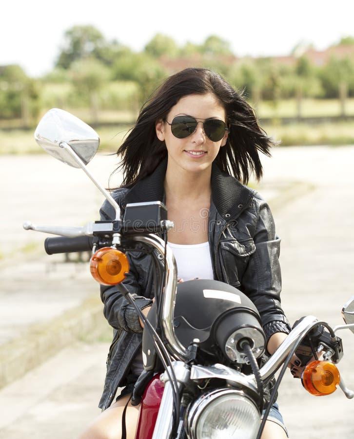 摩托车的逗人喜爱的妇女 免版税库存图片
