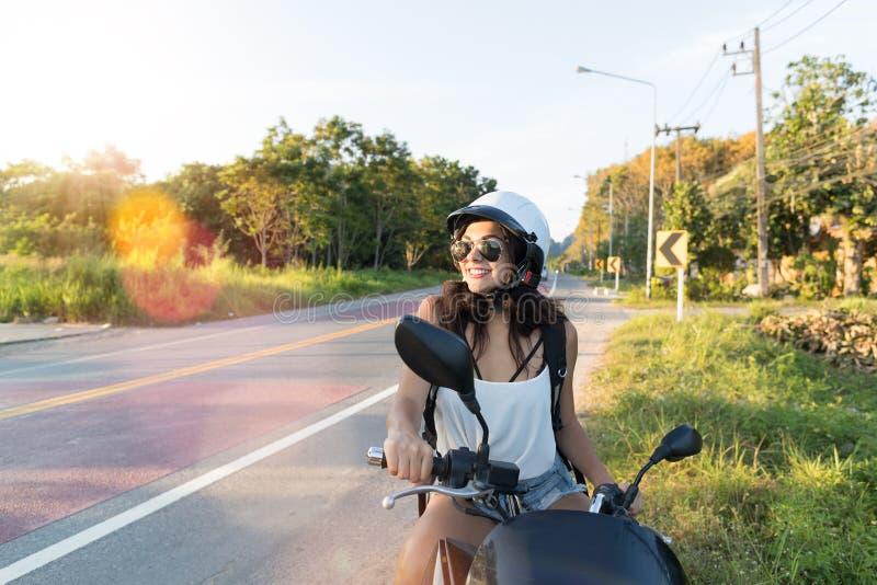 摩托车穿戴的Helemt可爱的妇女在摩托车的乡下路俏丽的妇女摩托车骑士旅行 免版税库存图片