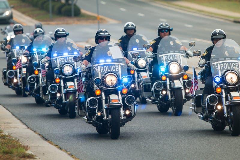 摩托车警骑自行车的人的形式伴游慈善自行车乘驾的 免版税库存照片