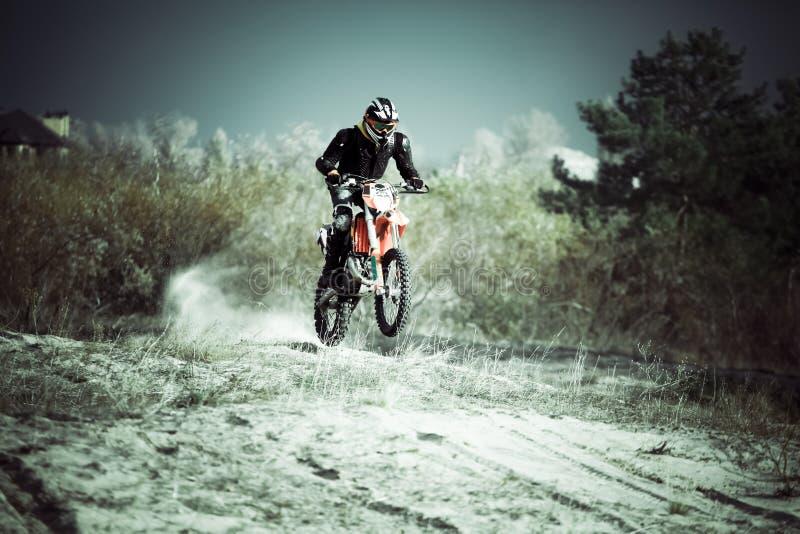 摩托车越野赛车手乘驾在沙子的土自行车 库存图片