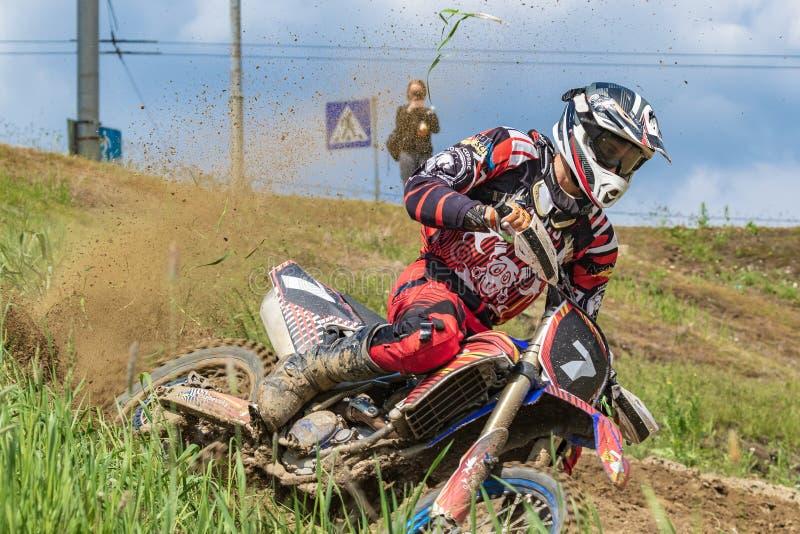 摩托车越野赛 摩托车骑士沿土路,土冲从轮子下面飞行 绿色植被和天空蔚蓝 免版税库存图片