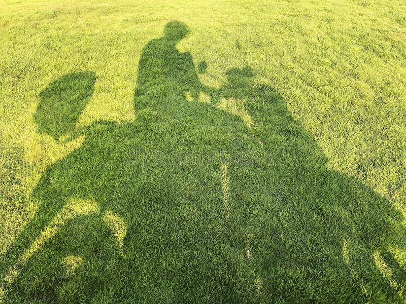 摩托车驾驶员的阴影在草的 库存图片