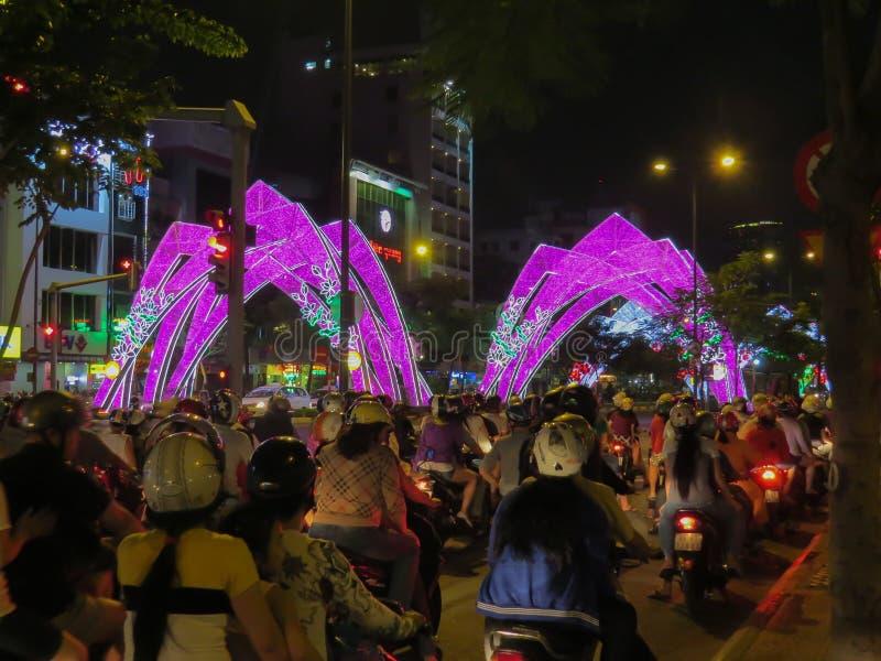 摩托车骑士是在红灯在下班时间在街市 城市是装饰的有启发性曲拱 免版税库存图片