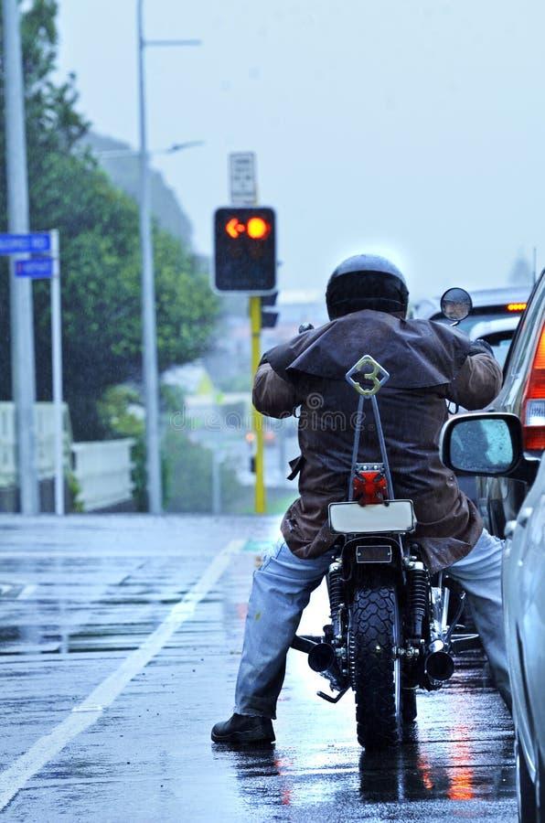 摩托车骑自行车的人骑马在早晨城市交通的雨中 图库摄影
