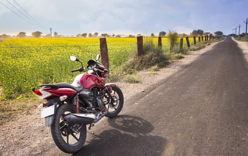 摩托车介于中间的领域和路 免版税图库摄影