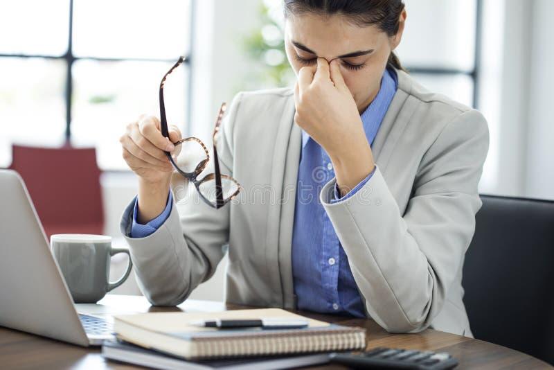 摩擦她的女实业家疲倦了眼睛 免版税库存图片