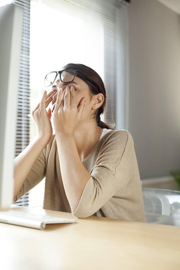 摩擦她的女实业家疲倦了眼睛 库存图片