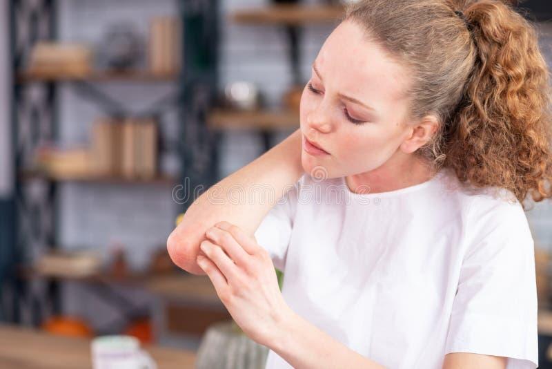 摩擦她的被察觉的手肘的困厄的不快乐的少女 免版税库存照片