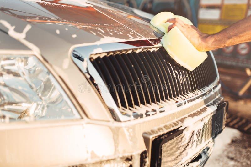 摩擦汽车的男性手用泡沫,洗车 免版税库存照片