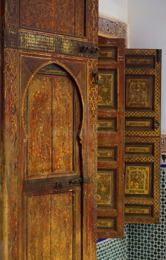 摩洛哥,马拉喀什 中世纪被绘的木窗口快门盘区的细节和锁伊斯兰教-蔓藤花纹样式 库存图片