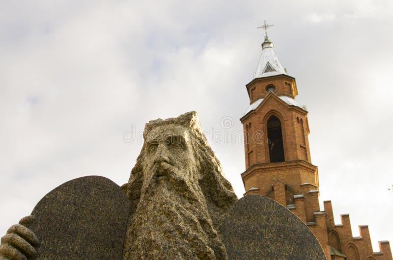 摩西雕象和一个哥特式教会的钟楼在背景中 库存照片