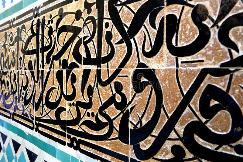 摩洛哥人Zellige瓦片样式和被雕刻的膏药蔓藤花纹曲拱在14世纪El Attarine Medersa在菲斯,摩洛哥 免版税库存图片