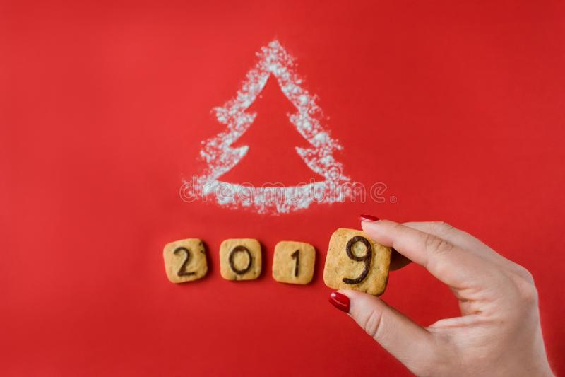 撒粉于剪影与曲奇饼数字的圣诞树2019年在红色 免版税库存图片