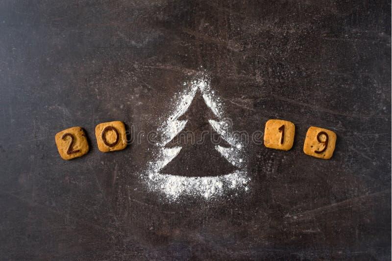 撒粉于剪影与曲奇饼数字的圣诞树2019年在黑暗 库存照片