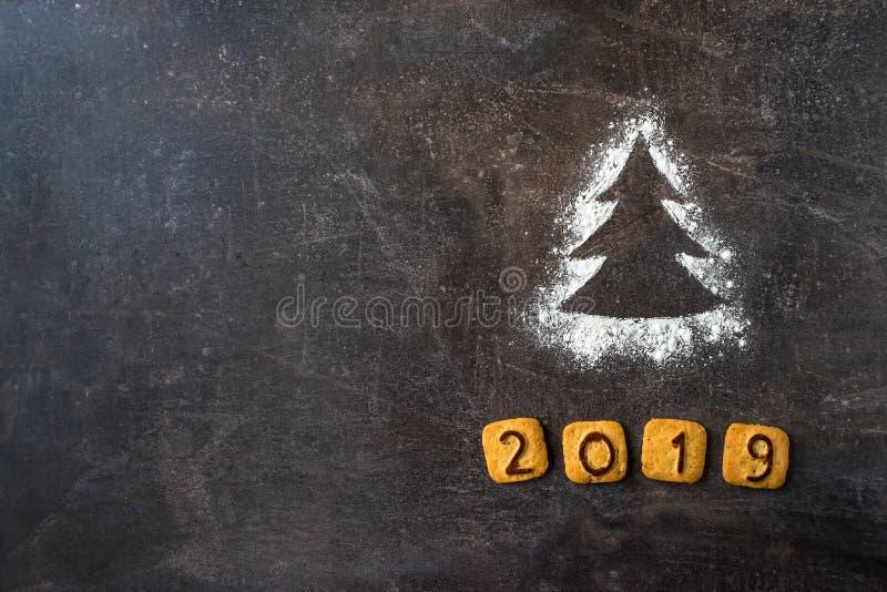 撒粉于剪影与曲奇饼数字的圣诞树2019年在黑暗 免版税库存图片