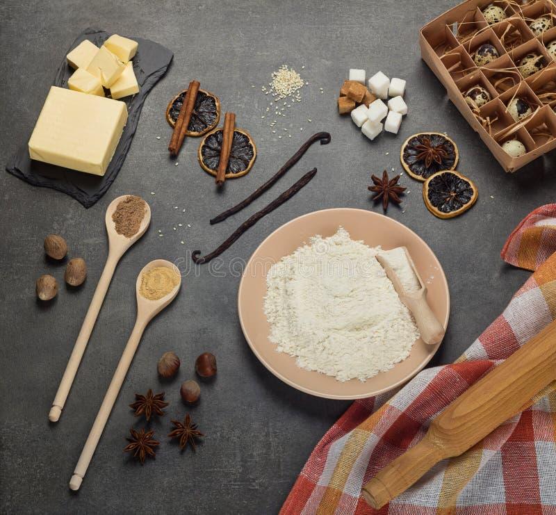 撒粉于在板材、套烘烤的产品和香料,在灰色背景 库存照片
