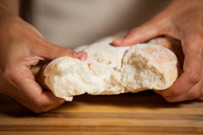 撕毁一个小圆面包的男职工在面包店商店 免版税库存图片