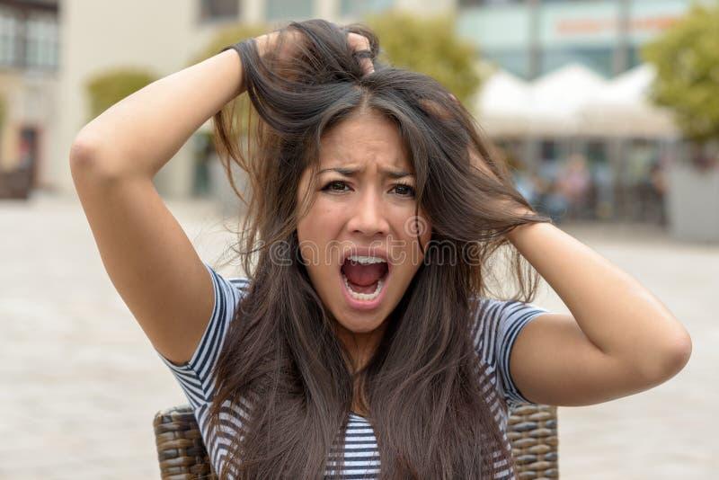 撕毁在她的头发的生气狂热少妇 免版税库存照片