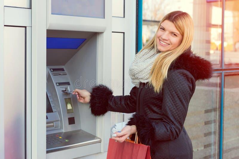 撤出从信用卡的少妇金钱在ATM现钞机 免版税库存图片