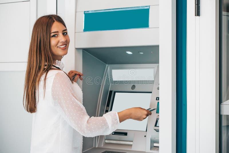 撤出从信用卡的微笑的妇女金钱在ATM 库存图片