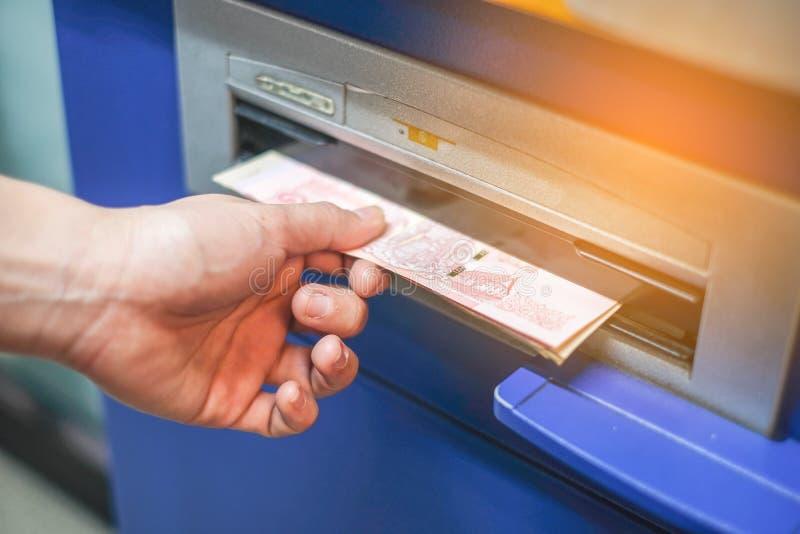撤出从银行ATM机器的妇女手金钱 免版税库存图片