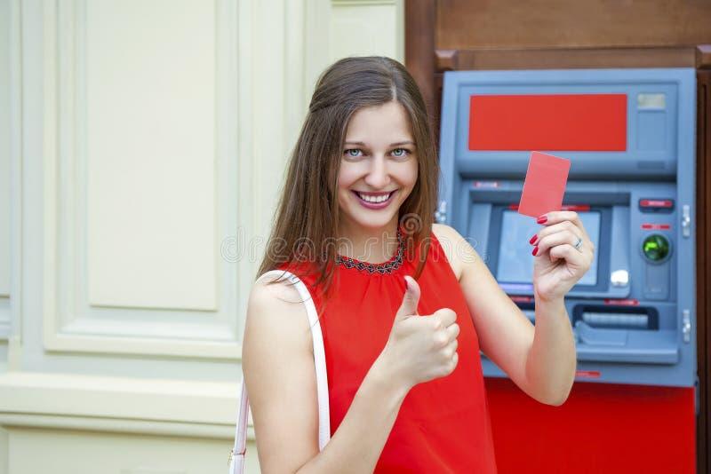 撤出从信用卡的少妇金钱在ATM 免版税库存照片