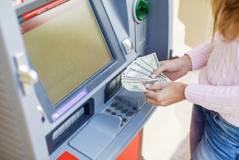 撤出从室外银行ATM的妇女手金钱 免版税库存图片