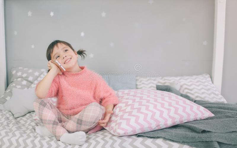 播放一个巧妙的电话,智能手机的逗人喜爱的女婴有对您的儿童s发展和精神健康的消极冲击 免版税图库摄影