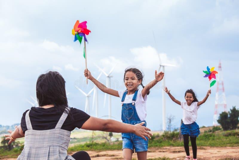 播放与风轮机玩具和赛跑的两个亚裔女孩对他们的母亲拥抱在风轮机领域的  免版税库存照片