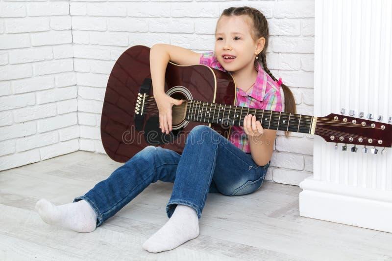播放吉他和唱歌的小女孩 免版税库存照片