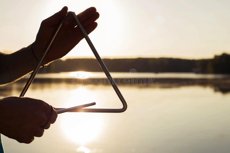 播放在背景天空的一个乐器三角在日落 免版税库存照片