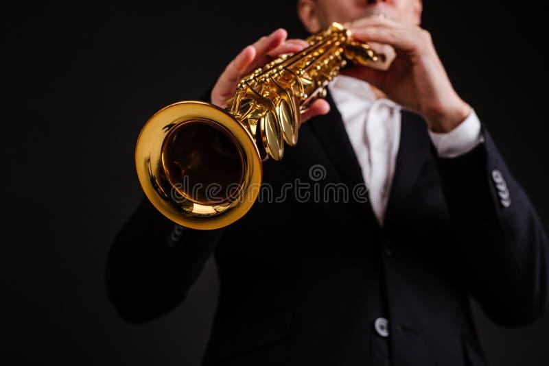 播放女高音萨克斯管特写镜头的一套黑经典衣服的萨克斯管吹奏者 免版税库存照片