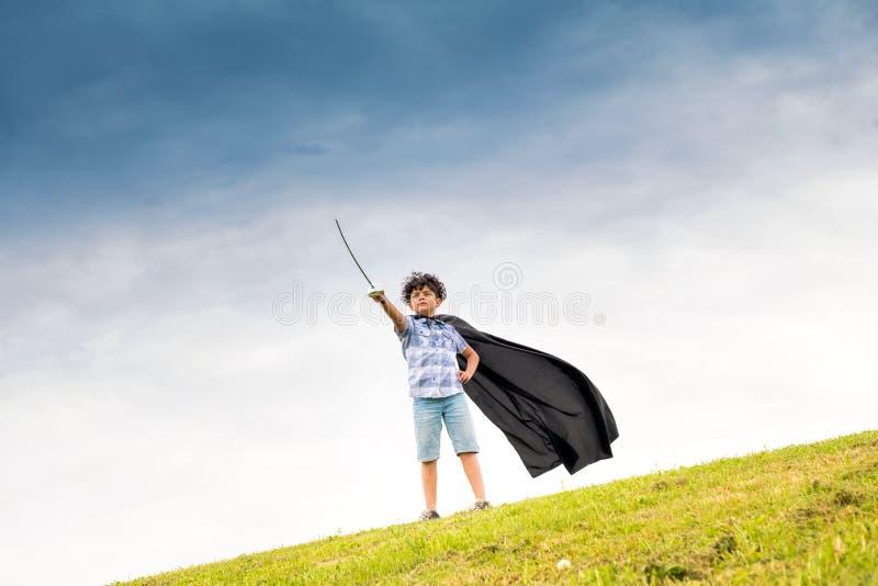 播放特级英雄的骄傲的年轻男孩 库存图片