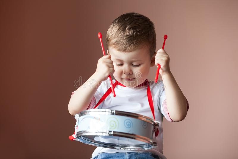 播放鼓的小男孩 儿童发育概念 免版税库存图片