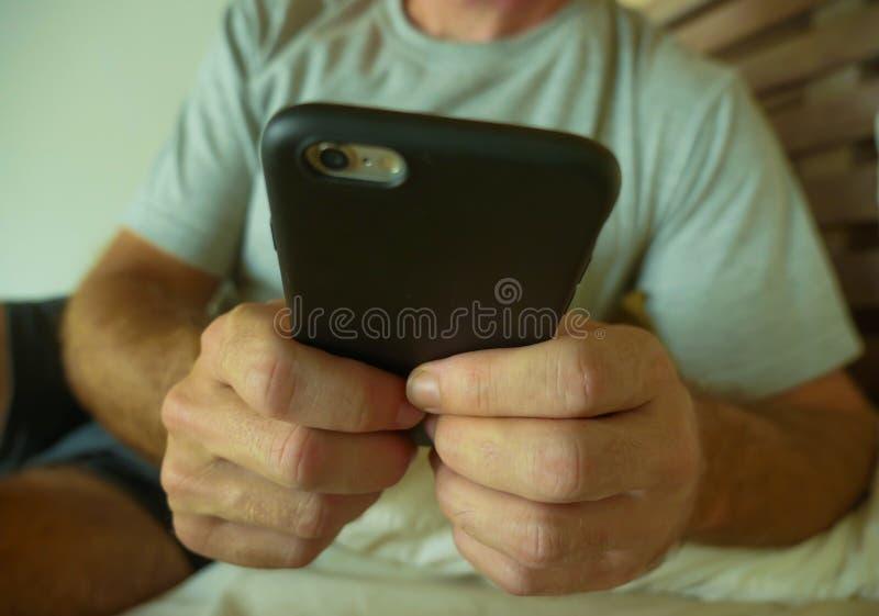 播种与关闭的面孔画象在家拿着年轻人卧室的手机手使用在smartp的互联网社会媒介app 免版税图库摄影