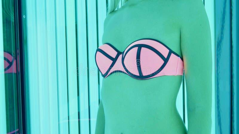 播种妇女的图象身体站立在晒黑的摊的桃红色和蓝色泳装的 库存照片