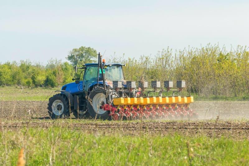 播种庄稼,农业领域在春天,有拖拉机种子的农夫 免版税库存照片