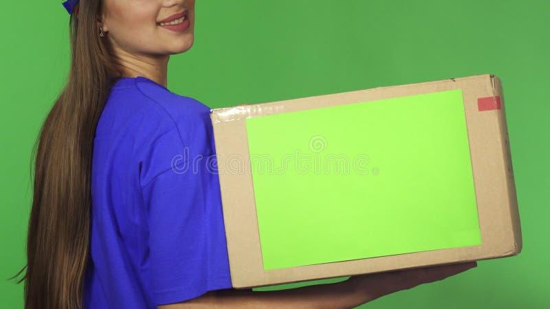 播种的后视图拿着纸板箱的射击了一名微笑的交付妇女 图库摄影