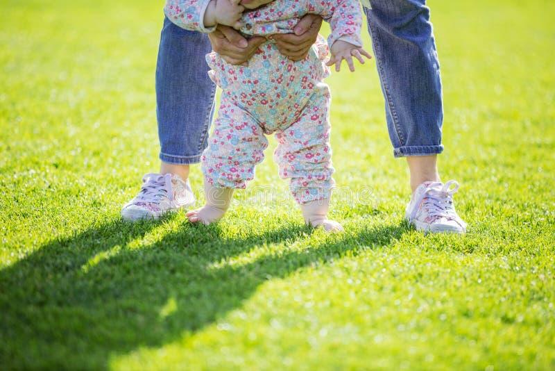 播种的看法母亲支持的小女儿和帮助她做第一步 免版税库存照片
