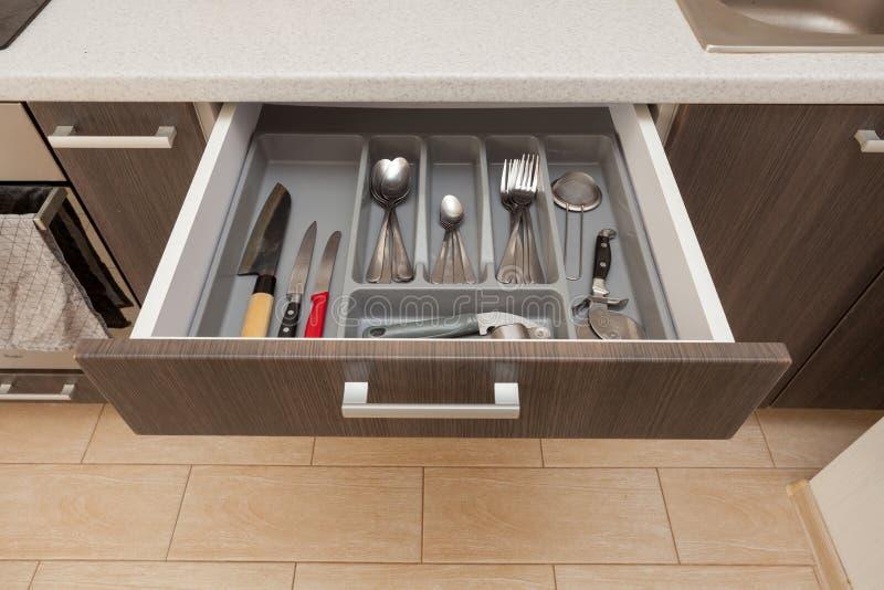 播种的部分干净的白色厨师worktop桌和开放新的现代木厨房抽屉大角度顶视图照片以不同 免版税库存照片