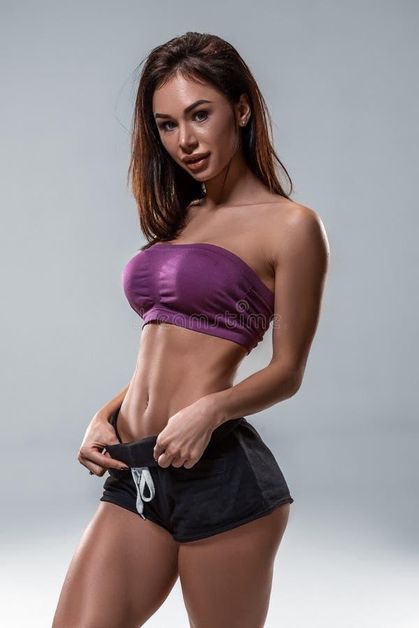 播种紧密适合妇女佩带的短裤和体育上面身体显示微小的美丽的胃和吸收的在饮食健身 库存照片