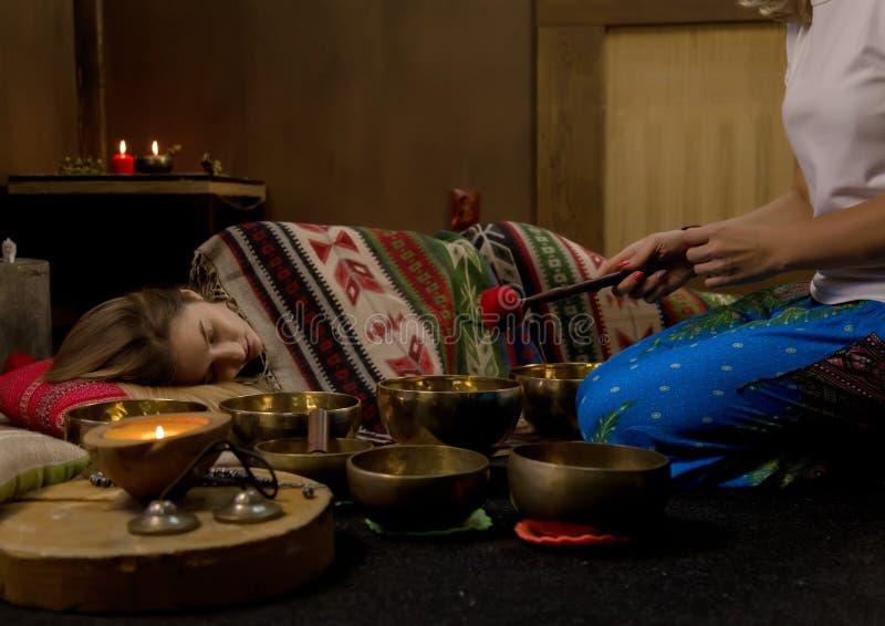 操作与西藏人唱歌碗的妇女 瑜伽辅导员举办凝思 慢的行动 免版税库存照片
