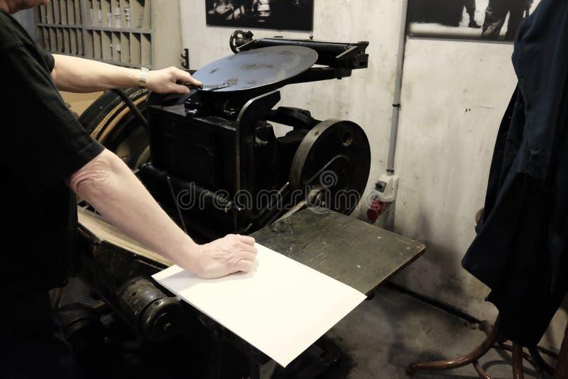 操作员在老印刷机器的工作 免版税库存图片